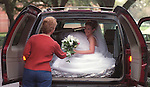 3/13/03--Bonnie Bogy, mother of bride-to-be Kimberly Bogy hands her daughter a boquet of flowers as they prepare to travel from Rice University to the Cancer Survivors Memorial.  Kimberly was having her wedding portrait shot at several locations around Houston and was riding in the back of a Chevrolet Suburban to try to keep her dress as unwrinkled as possible.  TEX MAG 12/28/2003.   HOUCHRON CAPTION (12/28/2003):  Bonnie Bogy, mother of bride-to-be Kimberly Bogy, hands her daughter a bouquet as they load up the car. For Kimberly, who was having her wedding portrait shot at several locations around Houston, it was a challenge to avoid wrinkling her dress.  03 YEAR IN REVIEW / REFLECTIONS / The news was dominated by images of war, but Houston Chronicle photographers reached beyond conflict to document local events and reassuring aspects of everyday life as well. / PICTURE PERFECT.