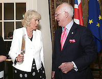 17 May 2016 - London, England - Camilla Duchess of Cornwall holds a knife after cutting a cake with Selwyn Image, founder of Emmaus UK, at a reception to celebrate the 25th anniversary of the charity - which supports former homeless people by giving them a home within one of its Emmaus Communities - at the French Ambassador's Residence in Kensington, London. Photo Credit: ALPR/AdMedia