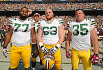 Green Bay Packers captains Cullen Jenkins, left, Scott Wells and Korey Hall pose for a group picture while quarterback Aaron Rodgers clowns around in the background before the Washington Redskins game at FedEx Field in Landover, Md., on Oct. 10, 2010.