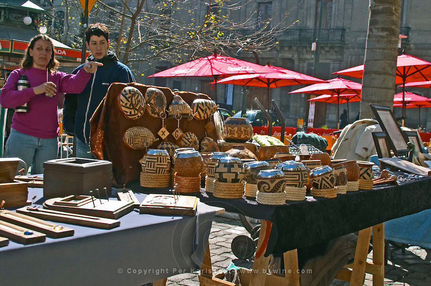 A street market stand, the merchant selling carved wooden cups with inlays and metal silver lining used for drinking mate herbal tea. Two people, one carrying the thermos flask, hot water bottle, so typical for mate drinkers in South America. Montevideo, Uruguay, South America