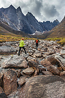 Day hiking across a boulder field in the Arrigetch Peaks, East and West Maiden and Camel peaks in the distance, Gates of the Arctic National Park, Alaska.
