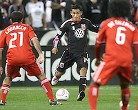 Andy Najar #14 of D.C. United sends a pass between Nick LaBrocca #21 and Julian de Guzman #6 of Toronto FC during an MLS match that was the final appearance of D.C. United's Jaime Moreno at RFK Stadium, in Washington D.C. on October 23, 2010. Toronto won 3-2.
