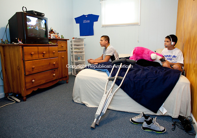 CHESHIRE, CT-29 August 2012-082912BF01-- Tyler Volpert, 10, right, and his brother Evan Volpert, 12, play video games in Tyler's room at their home in Cheshire. Tyler suffers from Perthes Disease, a condition that deteriorates the hip..Bob Falcetti Republican-American