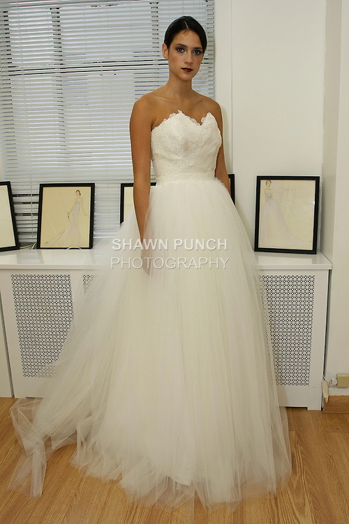 """Model poses in """"Iris"""" - a tulle ball gown with organza ruched bodice and lace appliques, from the Sarah Jassir Fall 2013: From Concept To Creation collection, for her Angelique Bridal store opening at 6 East 45 Street, during New York Bridal Fashion Week, October 15, 2012"""