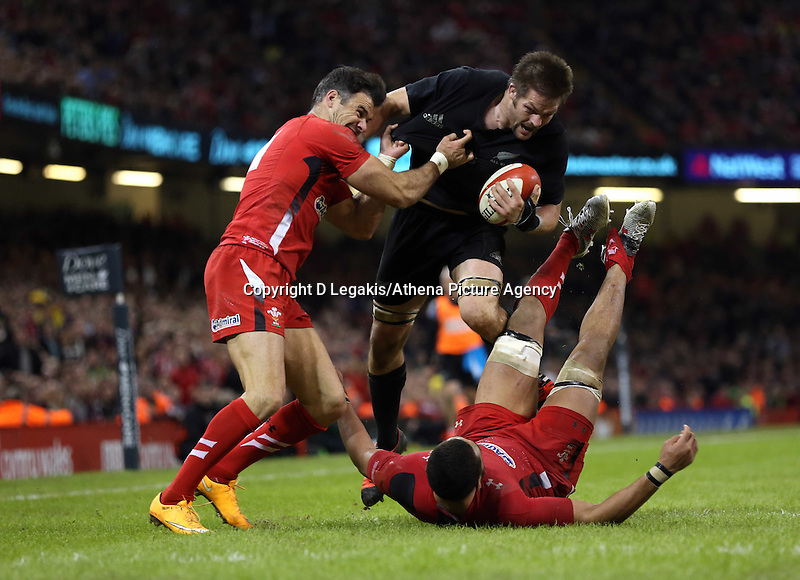 Pictured: Richie McCaw of New Zealand (C) is brought down by Mike Phillips of Wales (L) Saturday 22 November 2014<br /> Re: Dove Men Series 2014 rugby, Wales v New Zealand at the Millennium Stadium, Cardiff, south Wales, UK.