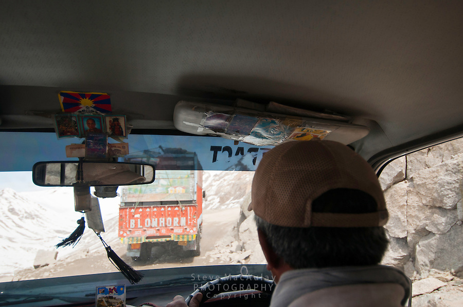View out of jeep window as it climbs the steep, rocky road up the highest motorable road in the world towards Khardung La at 18,380ft.  Himalayan Mountains, Ladakh, India.