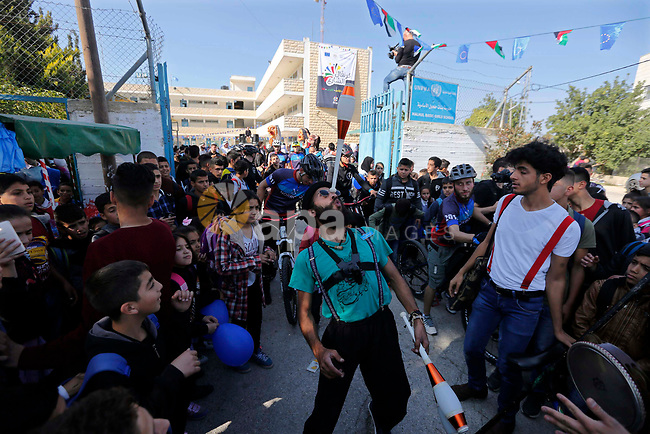 A clown performs in front of Palestinian students at a United Nations-run school during street carnival in the West Bank village of Halhoul near Hebron on November 19, 2018. Photo by Wisam Hashlamoun