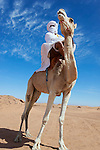 Nomad on dromedary in the Sahara desert against cloudy blue sky.
