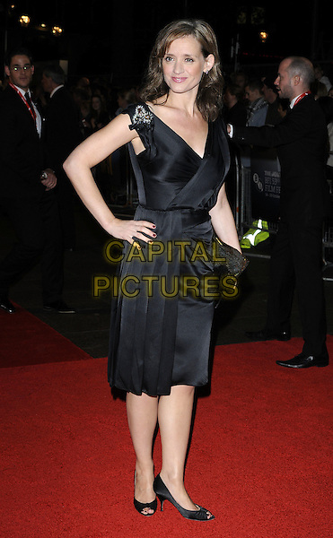 "ANNE-MARIE DUFF.The closing gala premiere of ""Nowhere Boy"" during the The Times BFI London Film Festival, Odeon Leicester Square, London, England..October 29th, 2009 .LFF full length black dress hand on hip wrap brooch clutch bag pleats pleated sleeveless .CAP/CAN.©Can Nguyen/Capital Pictures."