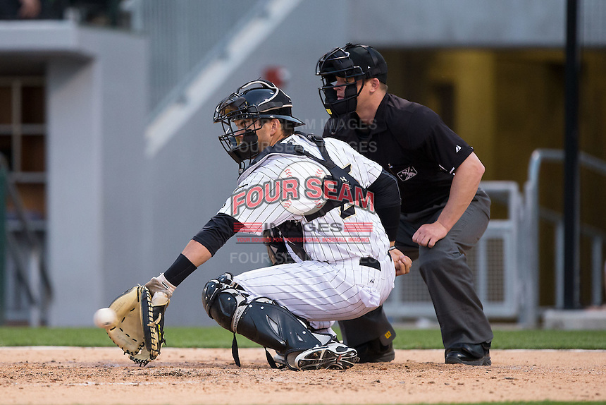 Charlotte Knights catcher Brett Austin (25) backhands a pitch as home plate umpire Ian Fazio looks on during the game against the Chicago White Sox at BB&T Ballpark on April 3, 2015 in Charlotte, North Carolina.  The Knights defeated the White Sox 10-2.  (Brian Westerholt/Four Seam Images)
