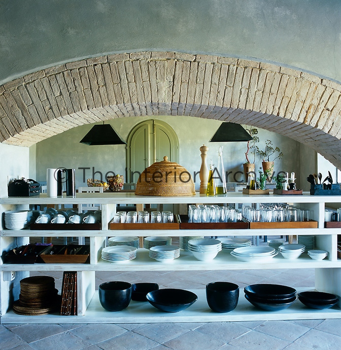 Crockery and glasses are stored in open shelving under a brick arch in the kitchen