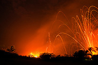 lava from Kilauea Volcano erupts at night from fissures in the east rift zone, Kapoho, near Pahoa, Puna, Big Island, Hawaii, USA, blasting glowing lava bombs high above the trees, into the starry sky (some lava ejecta reached heights well above 300m or 1000 feet)