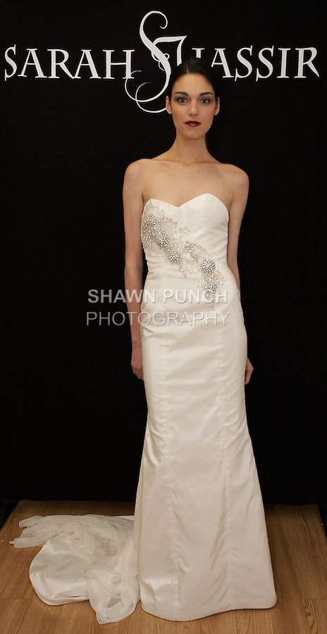 """Model poses in """"Selene"""" - a strapless taffeta gown with crystal beaded applique and front slit, from the Sarah Jassir Fall 2013: From Concept To Creation collection, for her Angelique Bridal store opening at 6 East 45 Street, during New York Bridal Fashion Week, October 15, 2012"""