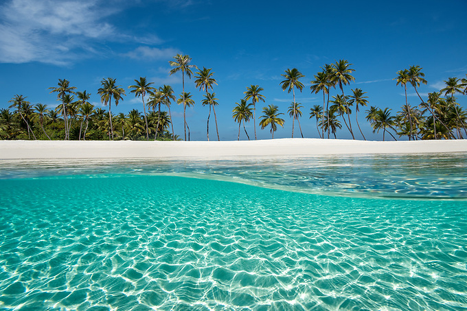 A unique view from above and below the aquamarine waters surrounding the white sand and palm trees on this picturesque island in the Indian Ocean.<br />