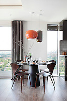 Orange and brown retro style pendant lights hanging above a round dining table with Norman Cherner chairs. The table has a table setting for four.