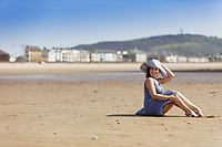 Holly Hughes enjoys the sunshine during what is believed to be the warmest day of the year so far, on the beach in Swansea Bay, Wales, UK. Friday 28 June 2019