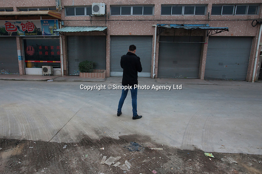 A man stands near the Yue Yuen Industrial Holdings Limited factory in Dongguan, Guangdong Province, China, 03 March 2015.
