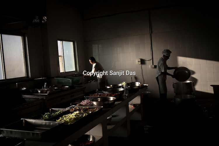 Chinese chefs prepare lunch in the kitchen of the Chinese colony of Adani Power plant in Mundra port industrial city of Gujarat, India. Indian power companies have handed out dozens of major contracts to Chinese firms since 2008. Adani Power Ltd have built elaborate Chinatowns to accommodate Chinese workers, complete with Chinese chefs, ping pong tables and Chinese television. Chinese companies now supply equipment for about 25% of the 80,000 megawatts in new capacity.