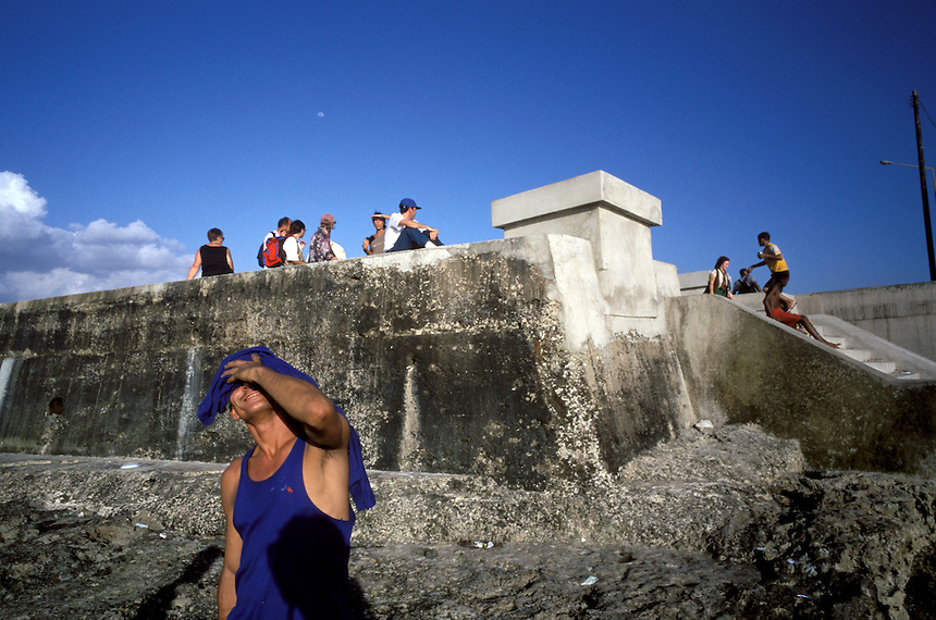 A street hustler named Hermes basks in the afternoon glow on Havana's Malecón sea wall.