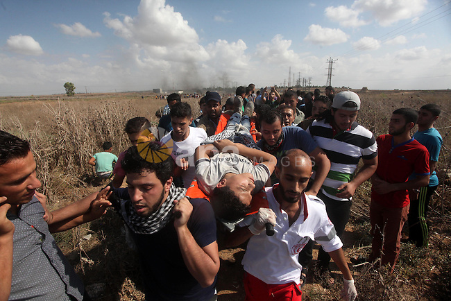 A Palestinian protester is evacuated by comrades after being injured during clashes with Israeli security forces near the border fence between Israel and the Gaza Strip on October 9, 2015 east of Gaza City. Tension and protests rose after an Israeli man on 09 October stabbed four Palestinians in southern Israel, in what is being seen as a revenge attack, officials said. On 08 October several violent incidents happened, including stabbings which left eight Israelis injured, one Palestinian was killed in East Jerusalem and six in the Gaza Strip in clashes with the army while at least six were injured on the West Bank. Photo by Ashraf Amra