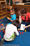 Education preschool 3-4 year olds psychology or education graduate student observing children play and making notes vertical