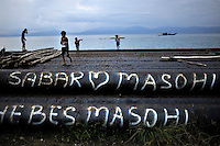 Children playing on top of metal pipes laid along the main port area of sleepy Masohi, the capital of Ceram Island. Graffiti reads 'Sabar heart Masohi' and 'Hebes Masohi'. /Felix Features