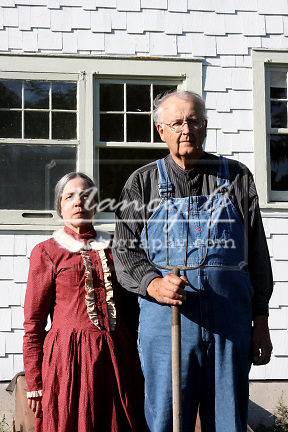 Woman and man posed in front of a white farm house with a pitchfork like the painting