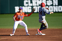 Second baseman Mac Starbuck (24) of the Clemson Tigers make the tag on Brett Paulsen (14) of the Stony Brook Seawolves in a game on Friday, February 21, 2020, at Doug Kingsmore Stadium in Clemson, South Carolina. Clemson won, 2-0. (Tom Priddy/Four Seam Images)