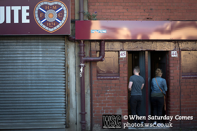 Heart of Midlothian 1 Birkirkara 2, 21/07/2016. Tynecastle Park, UEFA Europa League 2nd qualifying round. Two home supporters paying in at a turnstile in the historic old main stand at Tynecastle Park, Edinburgh before Heart of Midlothian played Birkirkara of Malta in a UEFA Europa League 2nd qualifying round, second leg. The match ended in victory for the Maltese side by 2-1 and they progressed on aggregate after the first match had ended 0-0. The game was watched by 14301 spectators, including 56 visiting fans of Birkirkara. Photo by Colin McPherson.