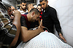 Relatives of Palestinian Abdul Karim Radwan, who was killed in an Israeli air strike, mourn over his body at a hospital in Rafah in the southern of Gaza Strip July 19, 2018. Photo by Ashraf Amra