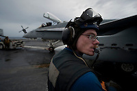 120507-N-DR144-040 PACIFIC OCEAN (May 7, 2012) Airman James McCaughan, assigned to the Air Department's V-1 Division, carries wheel chocks while moving an F/A-18C Hornet on the flight deck aboard the Nimitz-class aircraft carrier USS Carl Vinson (CVN 70). Carl Vinson and Carrier Air Wing (CVW) 17 are deployed to the 7th Fleet area of operations. (U.S. Navy photo by Mass Communication Specialist 2nd Class James R. Evans/Released)