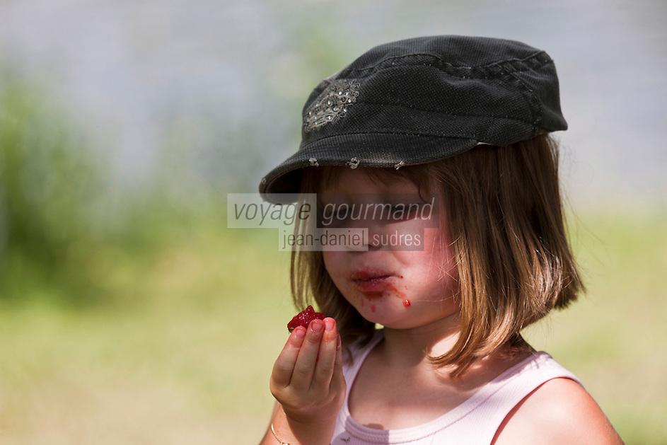 Europe/France/Aquitaine/24/Dordogne/Périgueux: Enfant mangeant des fraises lors d'un pique-nique sur  la voie verte qui longe l'Isle et traverse l'agglomération [Autorisation : 2011-114]