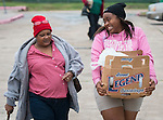A student volunteer carries a box of donated food for a Sunnyside resident at Worthing High School, November 22, 2013.