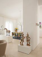 A white, spacious open-plan room with a sand-blasted stone floor. A contemporary Leda chandelier hangs above a bespoke bleached oak dining table and chairs. Various pieces of artwork are displayed around the room.