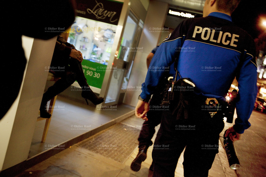 "Switzerland. Geneva. Two police officers at night on the streets of the Paquis neighborhood, known for its nightlife and Red-light district. The policeman (R) holds a pepper spray in his hand. Street prostitution. Most of the prostitutes work in the streets. Prostitution is often referred to as ""the world's oldest profession"". Both policemen are wearing a ballistic vest, bulletproof vest or bullet-resistant vest which is an item of personal armor that helps absorb the impact from knives, firearm-fired projectiles and shrapnel from explosions, and is worn on the torso. Soft vests are made from many layers of woven or laminated fibers and can be capable of protecting the wearer from small-caliber handgun and shotgun projectiles, and small fragments from explosives such as hand grenades. Pepper spray, also known as OC spray (from ""Oleoresin Capsicum""), OC gas, and capsicum spray, is a lachrymatory agent (a chemical compound that irritates the eyes to cause tears, pain, and even temporary blindness) used in policing. Its inflammatory effects cause the eyes to close, taking away vision. This temporary blindness allows officers to more easily restrain subjects. 17.03.12 © 2012 Didier Ruef"