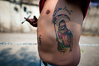 A Mexican follower of Santa Muerte (Saint Death) shows his tattoo during a religious pilgrimage in Tepito, a rough neighborhood of Mexico City, Mexico, 1 May 2011. The religious cult of Santa Muerte is a syncretic fusion of Aztec death worship rituals and Catholic beliefs. Born in lower-class neighborhoods of Mexico City, it has always been closely associated with crime. In the past decades, original Santa Muerte's followers (such as prostitutes, pickpockets and street drug traffickers) have merged with thousands of ordinary Mexican Catholics. The Saint Death veneration, offering a spiritual way out of hardship in the modern society, has rapidly expanded. Although the Catholic Church considers the Santa Muerte's followers as devil worshippers, on the first day of every month, crowds of believers in Saint Death fill the streets of Tepito. Holding skeletal figurines of Holy Death clothed in a long robe, they pray for power healing, protection and favors and make petitions to 'La Santísima Muerte', who reputedly can make life-saving miracles.