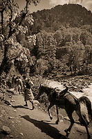 Toned black and white photograph of trekkers and horses walking along the Kanka River, Indian Himalaya, Kashmir, India