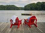 St. Andrew's School dock on Noxontown pond with two red adirondack chairs.