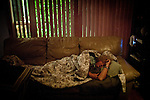 Unemployed and homeless, Liz Fenimore sleeps on a couch at her daughter's home in Sacramento, Calif. January 17, 2011.