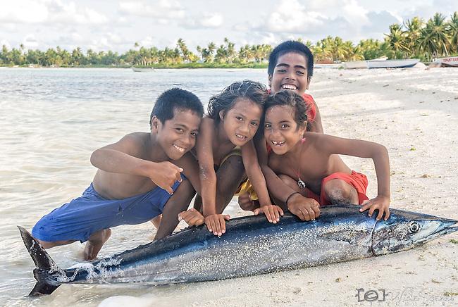i-Kiribati children posing for the camera with a fish in a village on the island of Kiritimati in Kiribati