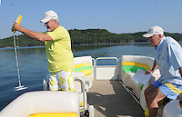 NWA Democrat-Gazette/FLIP PUTTHOFF<br /> 10 YEARS FOR SECCHI DAY<br /> Doug Wagley (left) and Andrew Sharpley measure the clarity of Beaver Lake on Saturday August 15 2015 during the 10th annual Secchi Day. Teams of volunteers fanned out on all areas of the lake to measure the water's transparency with a Secchi Disk. Data is compiled at Prairie Creek park where volunteers eat a complimentary lunch, see educational exhibits and win door prizes. Data from 10 years of Secchi Day events helps water officials spot any trends or changes in the clarity of the reservoir, said Bob Morgan with the Beaver Water District, which provides drinking water to most of the region. Beaver Lake is the drinking water source for Northwest Arkansas and beyond.