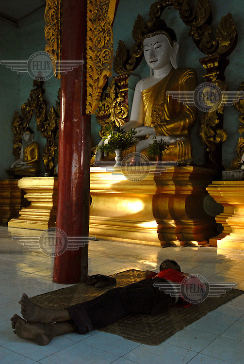 A young man asleep in the Shwekyimyint Paya. In a country where most people live in poor and cramped quarters, Burma's many pagodas are frequently used as public living spaces. The Shwekyimyint Paya shrine, founded in 1167 by Prince Minshinzaw, contains a Buddha image consecrated by the prince himself.