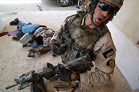A U.S. commander shouts orders to his men during a fire fight in Rawah, Iraq. Tuesday July 19, 2005