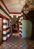 Bold stripes of red, white and dark brown line the walls of the ground floor apartment, while the floor is paved with geometrically patterned tiles