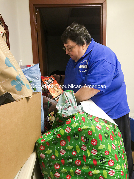 TORRINGTON, CT - 14 December 2015-121415EC03-- Gifts donated during the Christmas for Children Toy Drive, run by the Torrington Firefighters' Association, are organized by Maureen Hubert, Executive Director at the Friendly Hands Food Bank in Torrington Monday. Electronics, bikes, games and gift cards were among the items donated. The annual toy drive ends Tuesday. Erin Covey Republican-American.