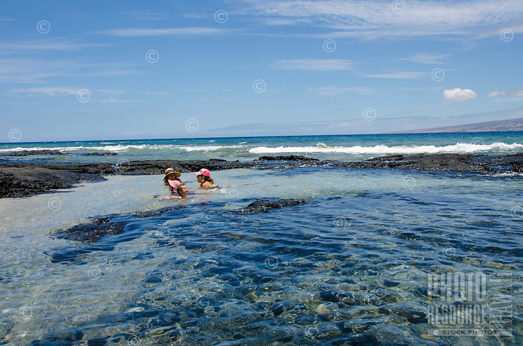 Two local children and their mothers talk and have fun while floating in tide pools at a beach in Puako, South Kohala, Big Island.