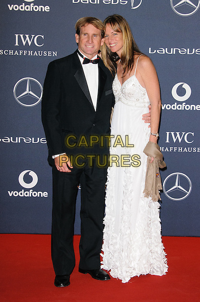 Robbie Naish & Katie.Arrivals at the Laureus 2012 World Sports Awards held at the Queen Elizabeth II Centre, London, England..February 6th, 2012.full length black tuxedo white dress married husband wife .CAP/CJ.©Chris Joseph/Capital Pictures.