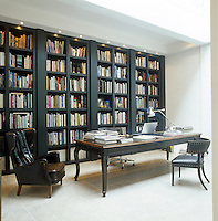 The library features a long writing desk and bespoke floor-to-ceiling bookshelves