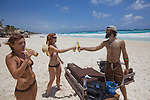 TULUM, MEXICO - APRIL 29, 2009: Adriana Mangino (L), of Mexico City, Dawnell Arthur (C) and Sam Nanfito (R), both from Denver, drink beer on the beach in front of Ocho Tulum on April 29, 2009 in Tulum, Mexico.  (PHOTOGRAPH BY MICHAEL NAGLE)