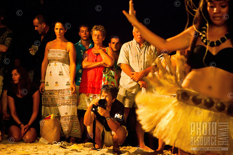 Visitors watching young beautiful Tahitian woman dancing